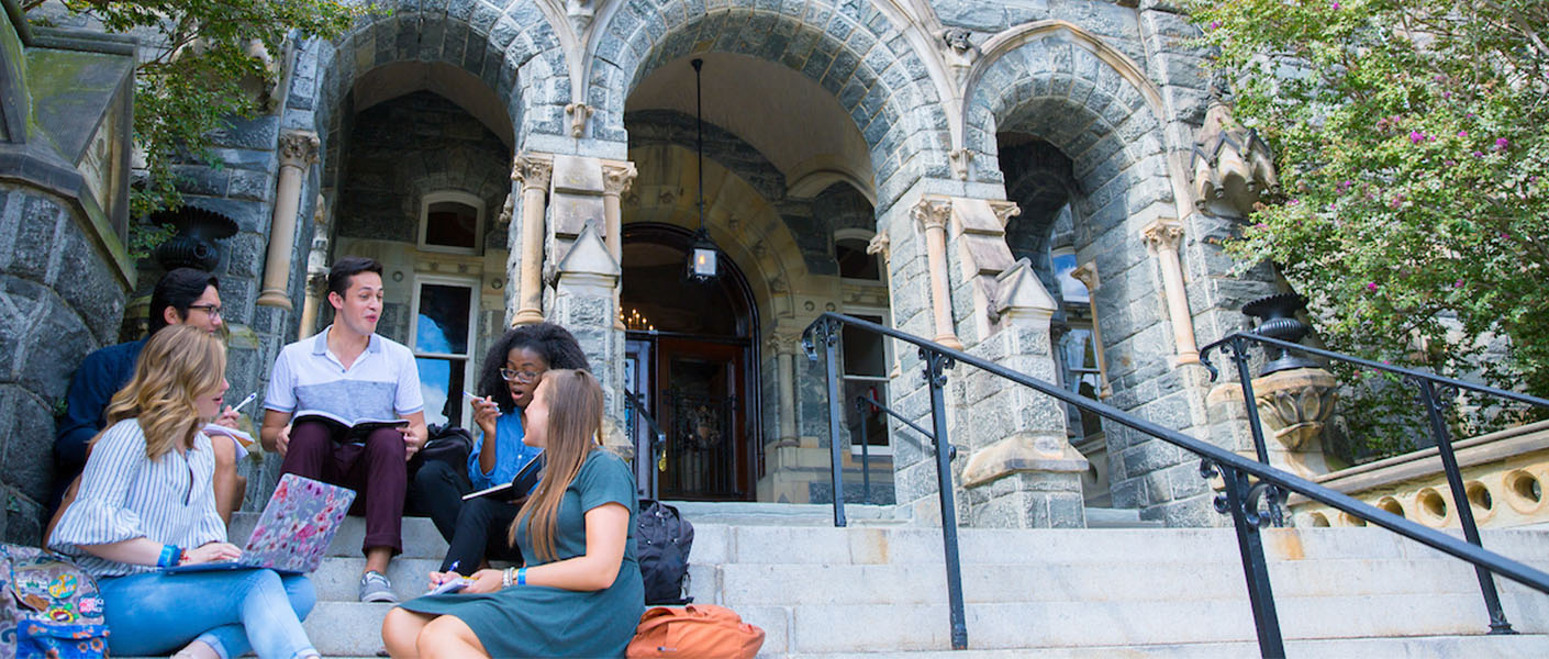 students sitting at the steps of healy hall